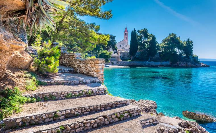Ancient-dominican-monastery-is-landmark-in-town-of-Bol-with-turquoise-beach-in-foreground-Island-of-Brac-Croatia.-Dominican-monastery-Bol-Brac