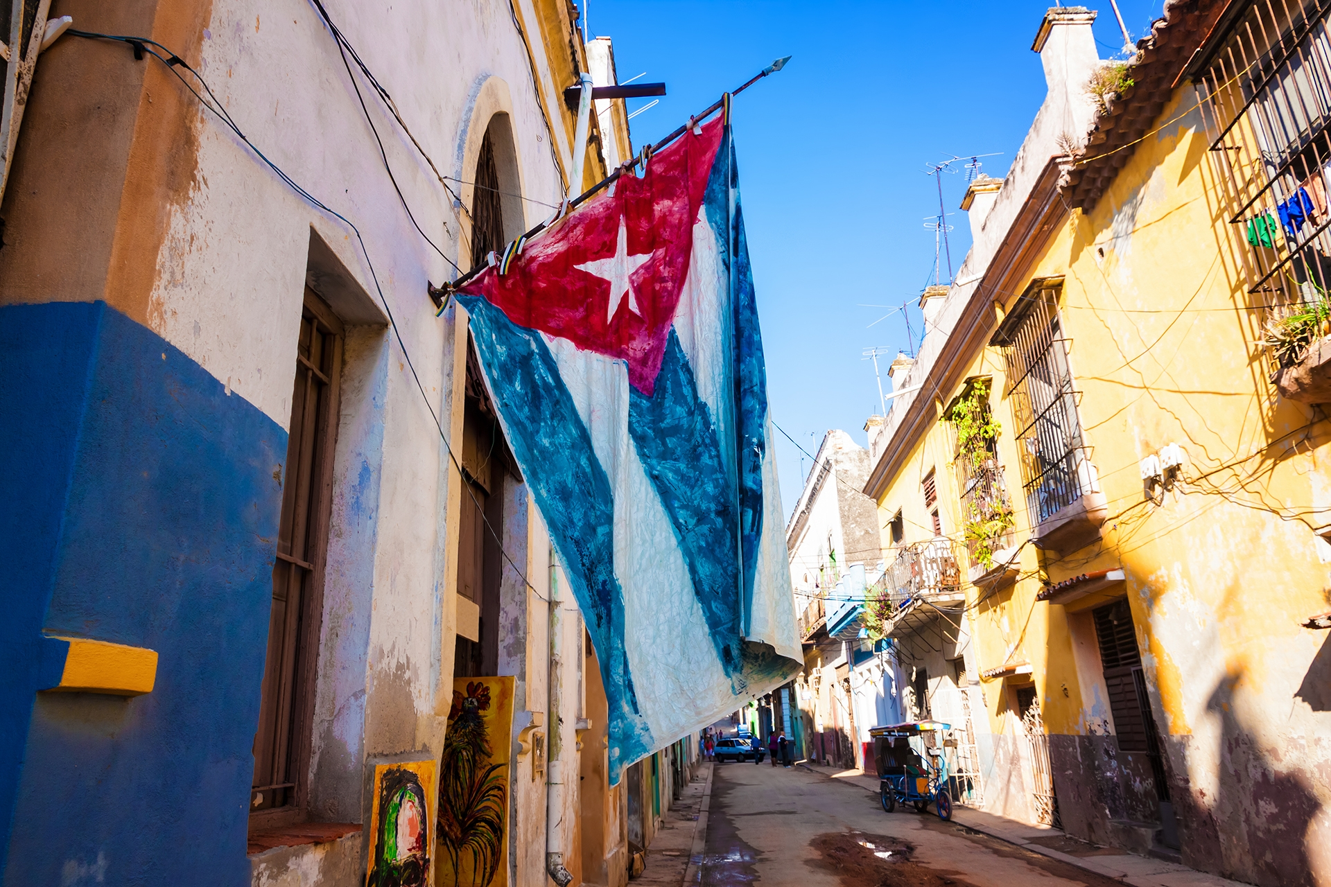 Street sidelined by decaying buildings in Old Havana with a big cuban flag