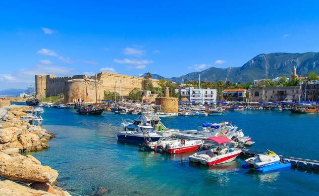 Boats in a port in Kyrenia Girne with castle in the background Cyprus