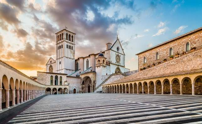 Famous-Basilica-of-St.-Francis-of-Assisi-Basilica-Papale-di-San-Francesco-with-Lower-Plaza-at-sunset-in-Assisi-Umbria-Italy