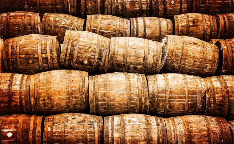 Stacked-pile-of-old-whisky-and-wine-wooden-barrels-in-vintage