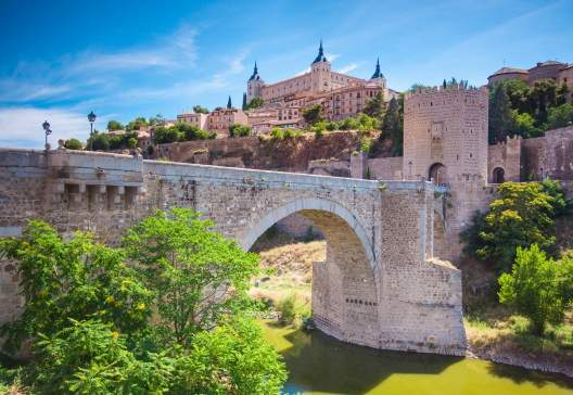 Panorama of the alcazar above the medieval San Martin bridge Toledo Spain