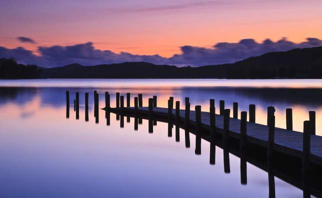 A-jetty-reflected-in-the-still-water-of-Coniston-Water-at-sunset