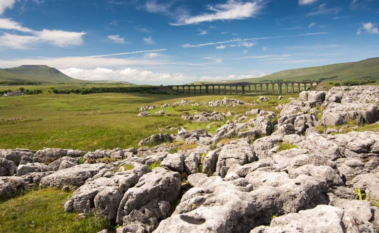 A-train-crossing-Ribblehead-Viaduct-in-the-Yorkshire-Dales-on-a-sunny-day-shot-from-the-limestone-pavement