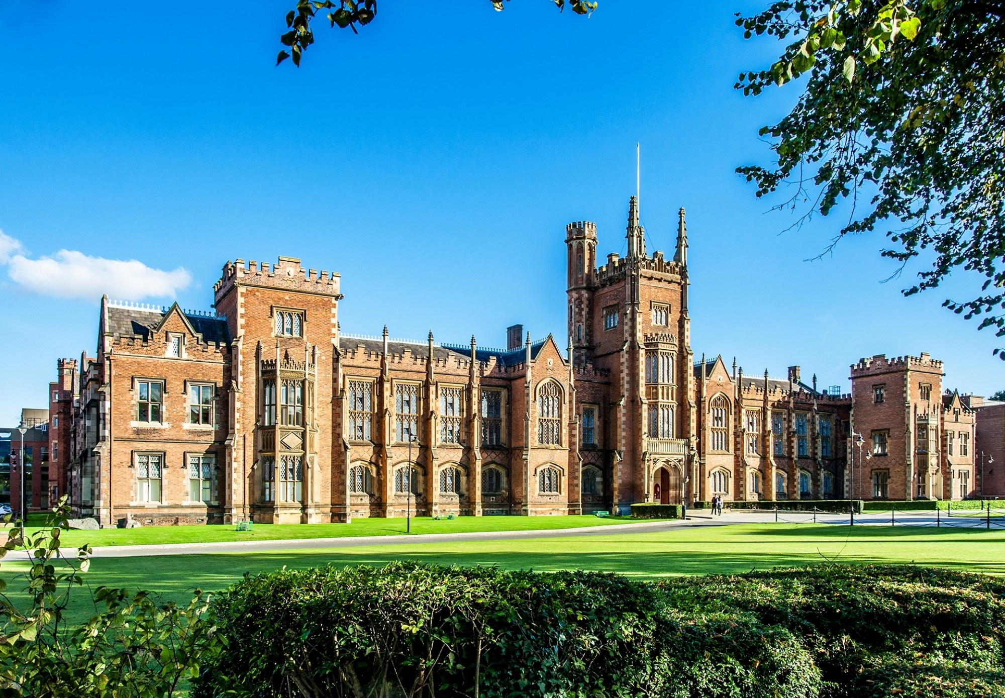 The-Queens-University-of-Belfast-with-a-grass-lawn-tree-branches-and-a-hedge-in-sunset-light